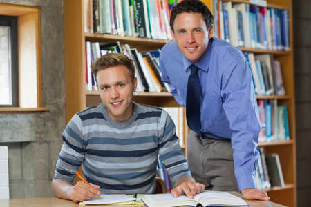 lecturer: Cheerful lecturer and student looking at camera in library in a college