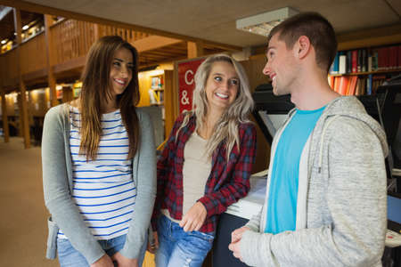 photocopier: Happy group of students standing next to photocopier in library in a college