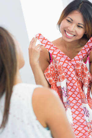 pijamada: Smiling beautiful woman trying on a top while looking at her sister LANG_EVOIMAGES