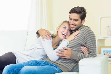 couple on couch: Laughing young couple sitting on couch cuddling LANG_EVOIMAGES
