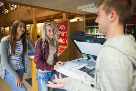 photocopier: Laughing group of students standing next to photocopier in library in a college