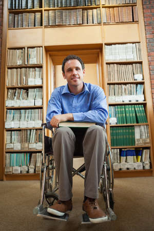 lucky man: Lucky man in wheelchair holding a book in library in a college