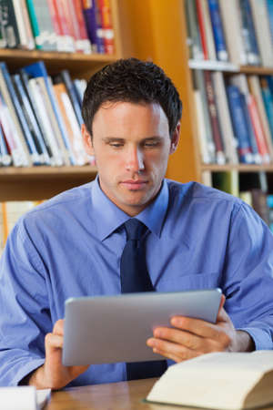 librarian: Calm librarian sitting at desk using tablet in library in a college LANG_EVOIMAGES