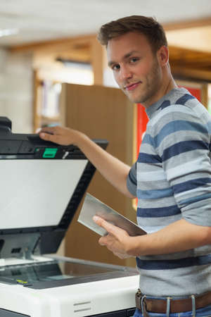 fotocopiadora: Happy handsome student using photocopier in library in a college