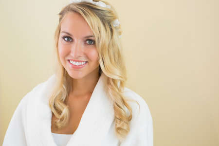 bath robe: Cheerful gorgeous bride smiling at camera wearing a bath robe