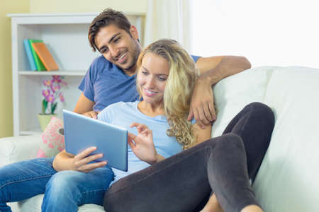 couple on couch: Young attractive couple sitting on a couch using a tablet LANG_EVOIMAGES