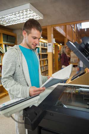 fotocopiadora: Feliz buena estudiante en busca de pie junto a la fotocopiadora de la biblioteca en un colegio