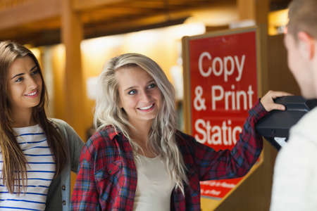 photocopier: Smiling group of students standing next to photocopier in library in a college