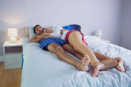 long hair man: Peaceful woman cuddling with her boyfriend lying on the bed LANG_EVOIMAGES