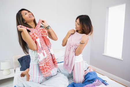 pijamada: Dos hermanas felices intentar algo de ropa de rodillas en una cama