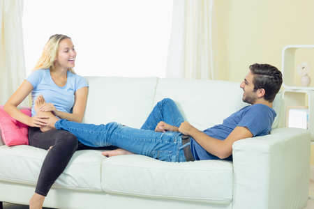 Happy blonde woman massaging the feet of her boyfriend sitting in the living room LANG_EVOIMAGES
