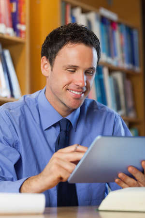 librarian: Cheerful librarian sitting at desk using tablet in library in a college LANG_EVOIMAGES