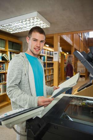 fotocopiadora: Sonriendo buen estudiante en busca de pie junto a la fotocopiadora en la biblioteca en una universidad