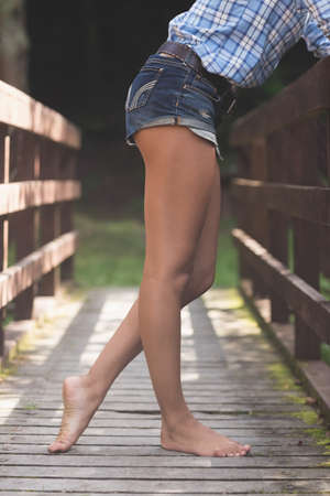 lower body: Side view of lower body of model leaning against bridge in nature