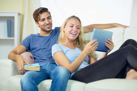 couple on couch: Happy couple using a tablet sitting on a couch holding a book LANG_EVOIMAGES