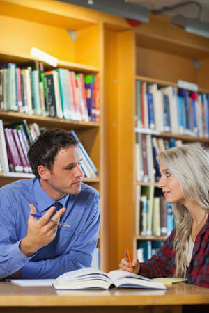 lecturer: Lecturer explaining something to attentive blonde student in library in a college