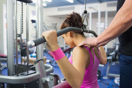 correcting: Instructor correcting shoulder position of woman of working out in weights room of gym