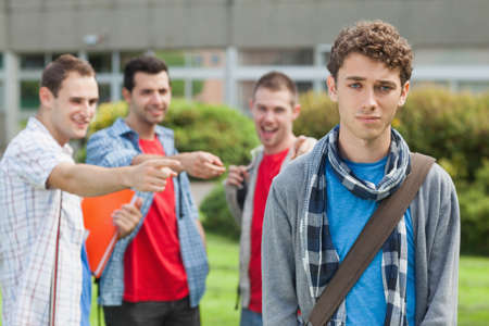 bullied: Lonely student being bullied by group of brutish classmates looking hopelessly at the camera at the university LANG_EVOIMAGES