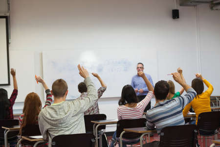 lecturing: Students listening to their teacher in classroom and raising their hands at the university LANG_EVOIMAGES