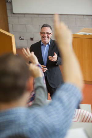 lecturer: Happy lecturer pointing at student raising his hand in college