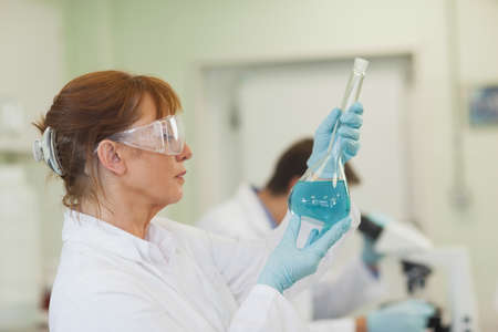 erlenmeyer: Profile view of female scientist holding an erlenmeyer flask standing in a laboratory
