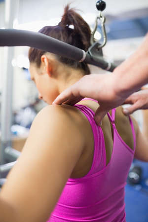 correcting: Instructor correcting shoulder position of woman working out in weights room of gym