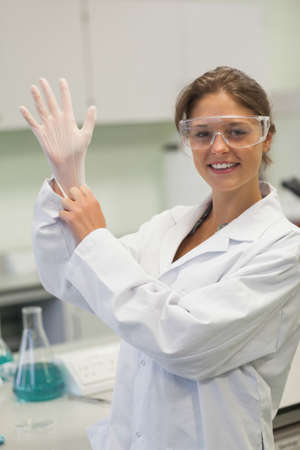 putting on: Attractive smiling student putting on rubber glove in lab in university