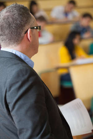 lecturer: Lecturer watching over his class in lecture hall in college