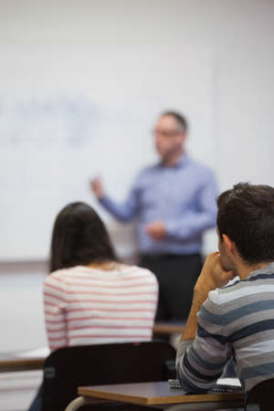 lecturer: Students listening to their lecturer in classroom at the university LANG_EVOIMAGES