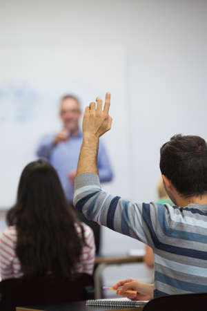 adult hand: Student raising his hand in class at the university