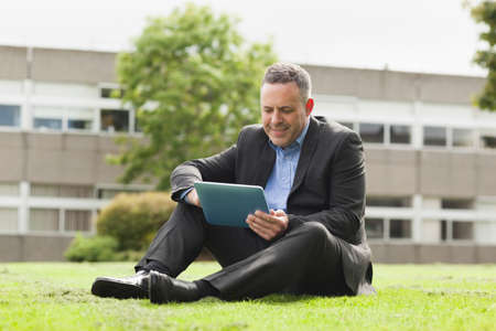 lecturer: Smiling lecturer using his tablet pc sitting outside on campus at the university