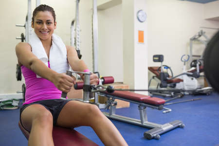 weight machine: Smiling woman training arms on weight machine in weights room of gym