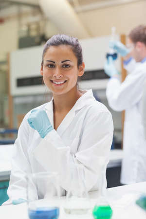bata de laboratorio: Smiling attractive student in lab coat looking at camera in lab at college
