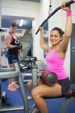 weight machine: Smiling brunette training at weight machine in weights room of gym