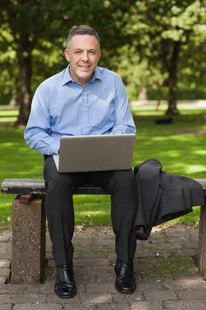 lecturer: Smiling lecturer sitting on bench using laptop on campus at the university