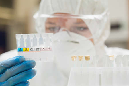 lab assistant: Lab assistant with mask looking at test results in lab at college