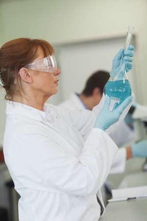 erlenmeyer: Female scientist holding an erlenmeyer flask in a laboratory