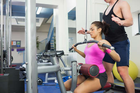 weight machine: Instructor assisting sporty brunette at weight machine in weights room of gym