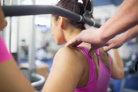 correcting: Instructor correcting shoulder position of brunette working out in weights room of gym