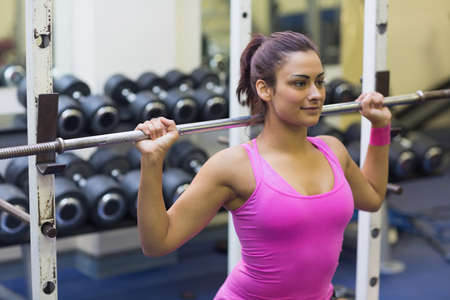 tied hair: Content brunette holding barbell in weights room of gym