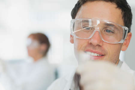 microscope slide: Handsome young scientist looking at microscope slide in a laboratory