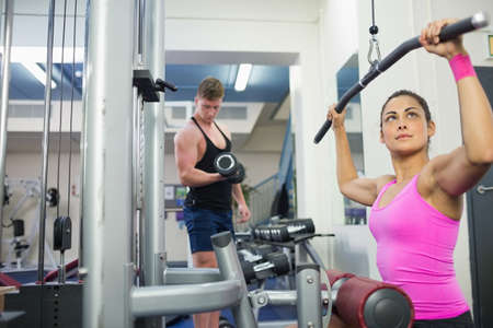 weight machine: Calm brunette training at weight machine in weights room of gym