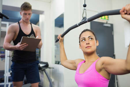 toning: Determined brunette training at weight machine in weights room of gym