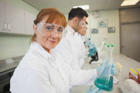 erlenmeyer: Content female scientist holding an erlenmeyer flask smiling at camera
