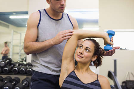 correcting: Trainer correcting content woman lifting dumbbells in weights room of gym LANG_EVOIMAGES