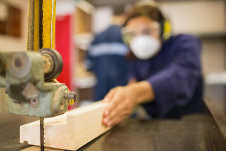 trainee: Trainee wearing safety protection using a saw in workshop LANG_EVOIMAGES