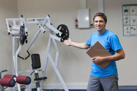 lat: Portrait of a smiling trainer with clipboard pointing toward the lat machine in the gym