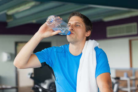 man drinking water: Tired young man drinking water while working out in the gym LANG_EVOIMAGES