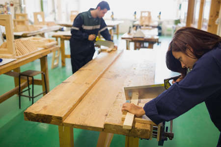 trainee: Focused trainee and instructor sawing wood in workshop