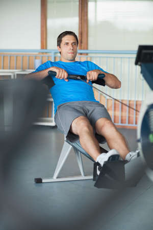 man working out: Full length of a determined young man working out on row machine in fitness studio LANG_EVOIMAGES